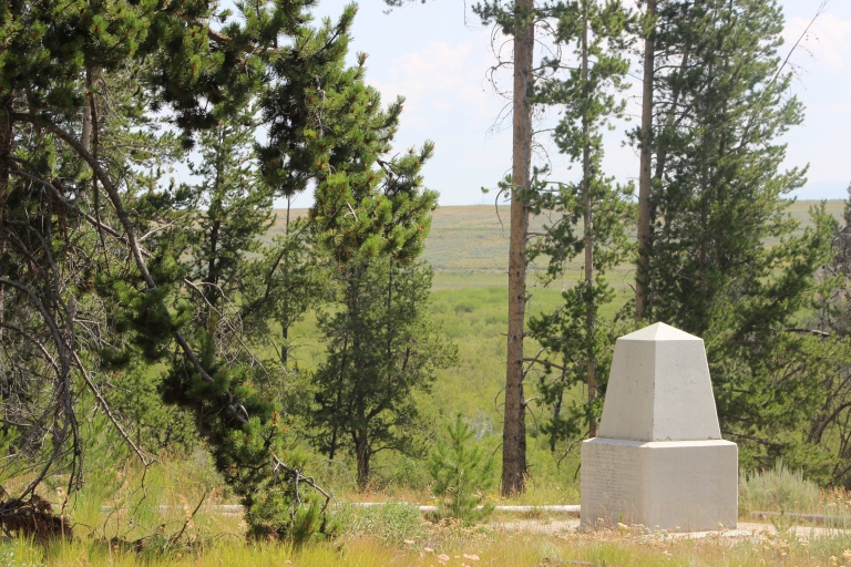 A small, white obelisk monument on the hillside surrounded by trees.