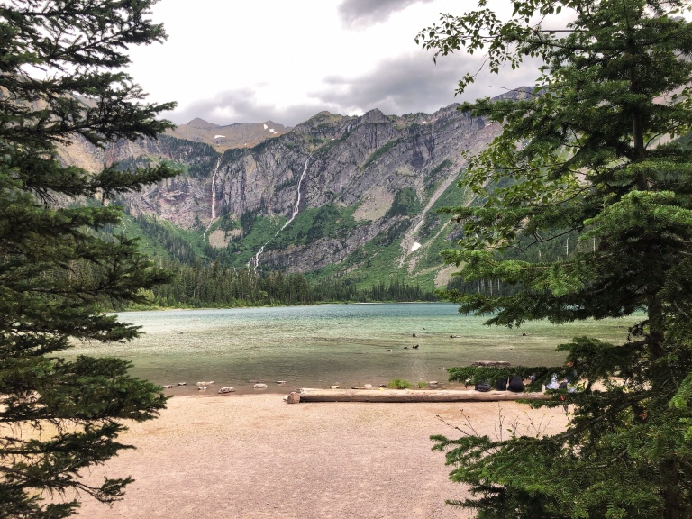 Two pine trees frame a lake with sheer mountain cliffs in the background